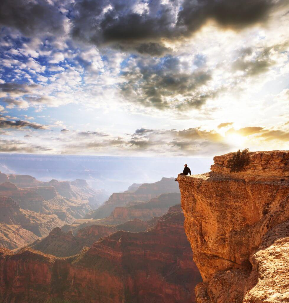 man sitting on the edge of the grand canyon